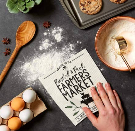 "Hand uses reusable dishcloth that says ""Bushel & Peck Farmers Market"" to wipe up flour on a kitchen table"