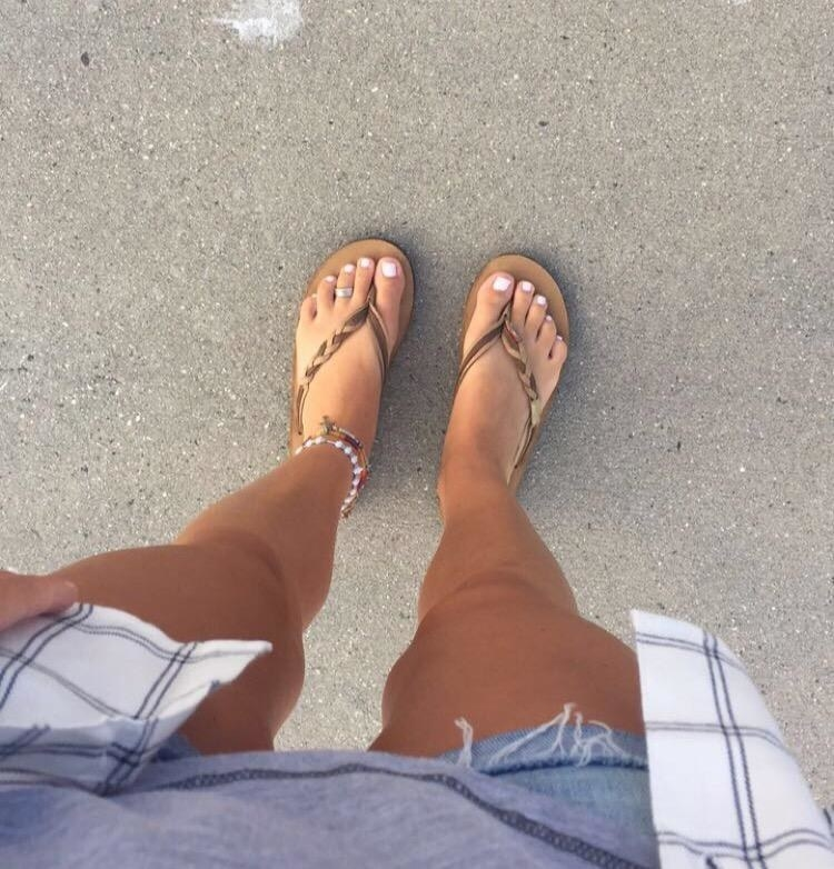 Reviewer wearing the tan sandals, which have one braided toe strap