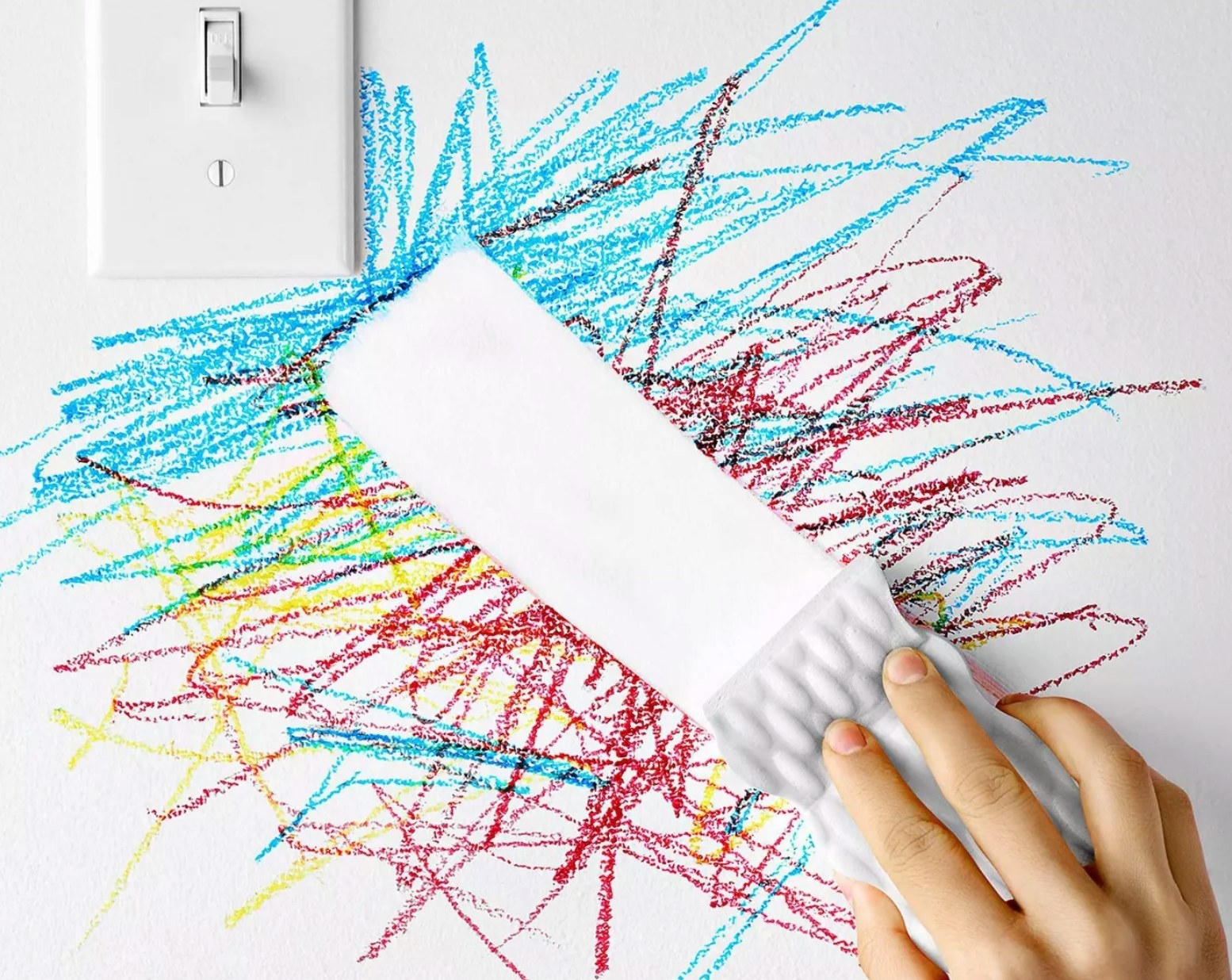 White magic eraser wipes away crayon drawings from a fridge