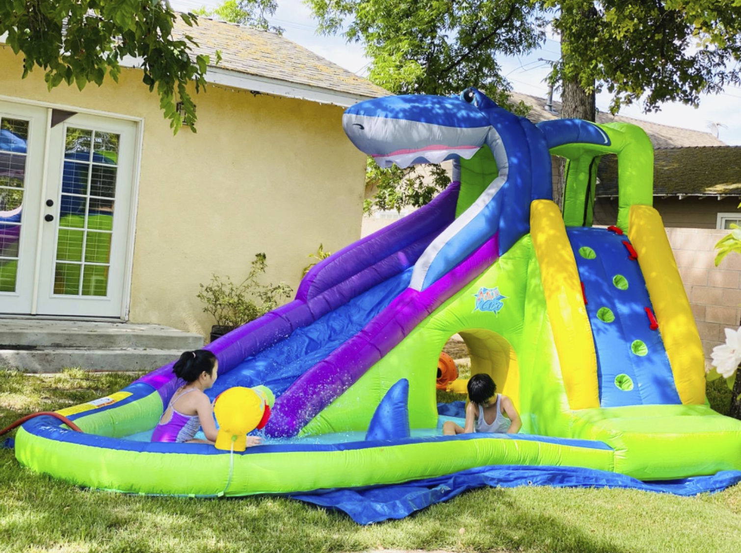 the blow-up slide with has a shark mouth at the top of the slide and a climbing slide on the side with foot rungs for climbing. Both slides have a small sitting area. The two slides are also connected by an open tunnel to crawl through.