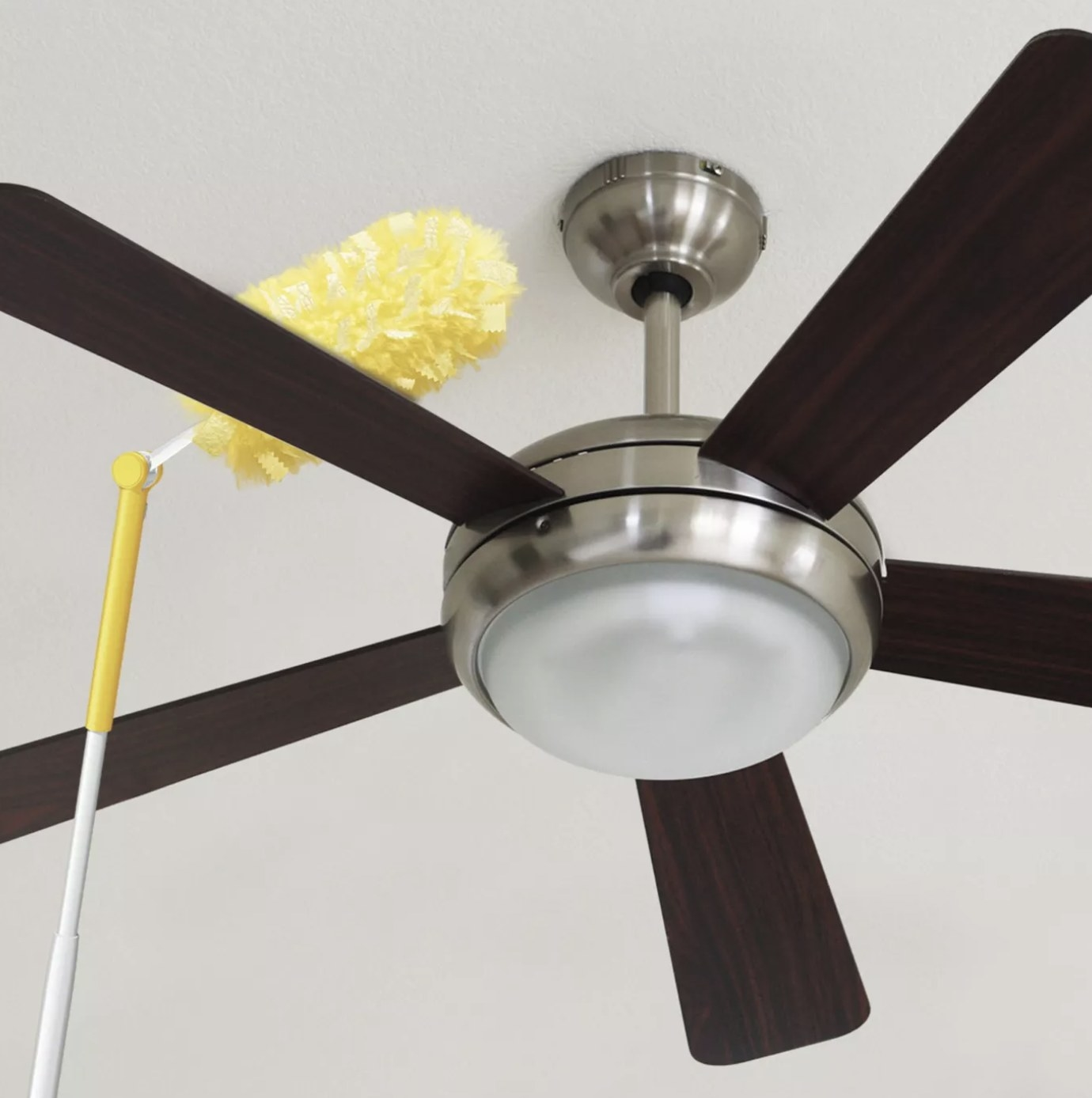 Yellow duster extends over the side of a brown fan to remove dust