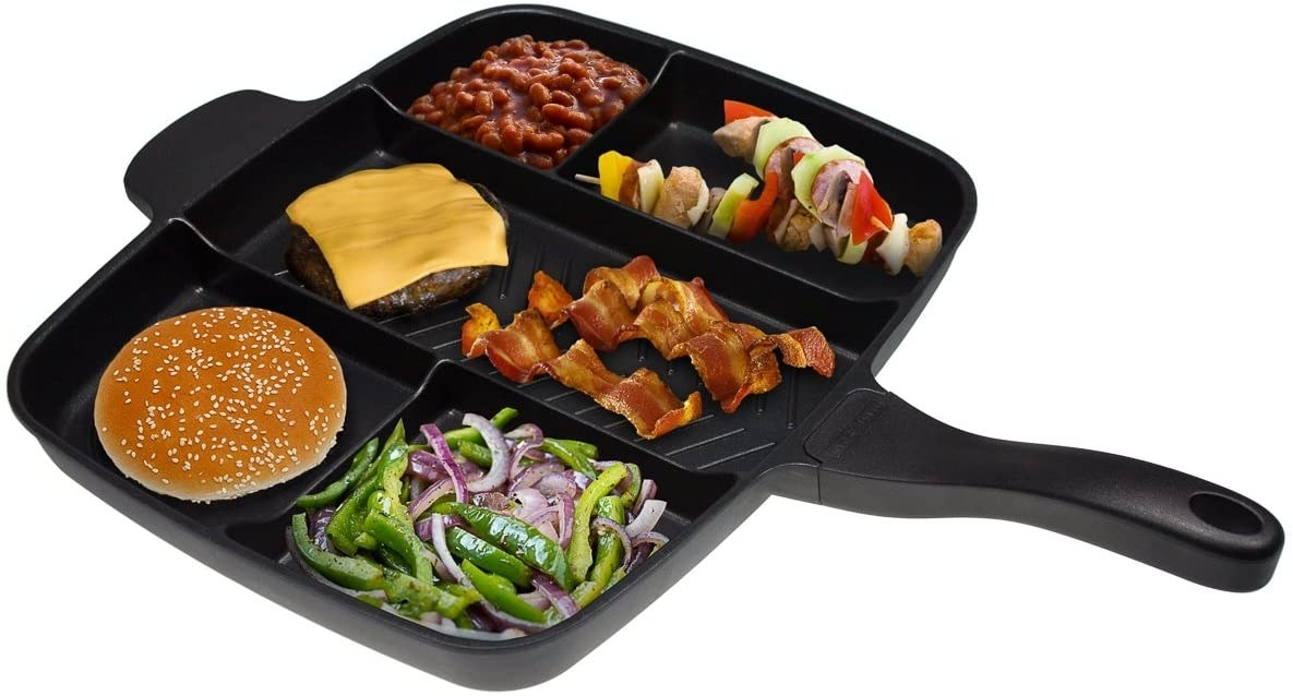 A rectangular non-stick skillet divided into sections, containing different foods like a burger bun, peppers and onions, bacon, a hamburger patty, and kebobs.