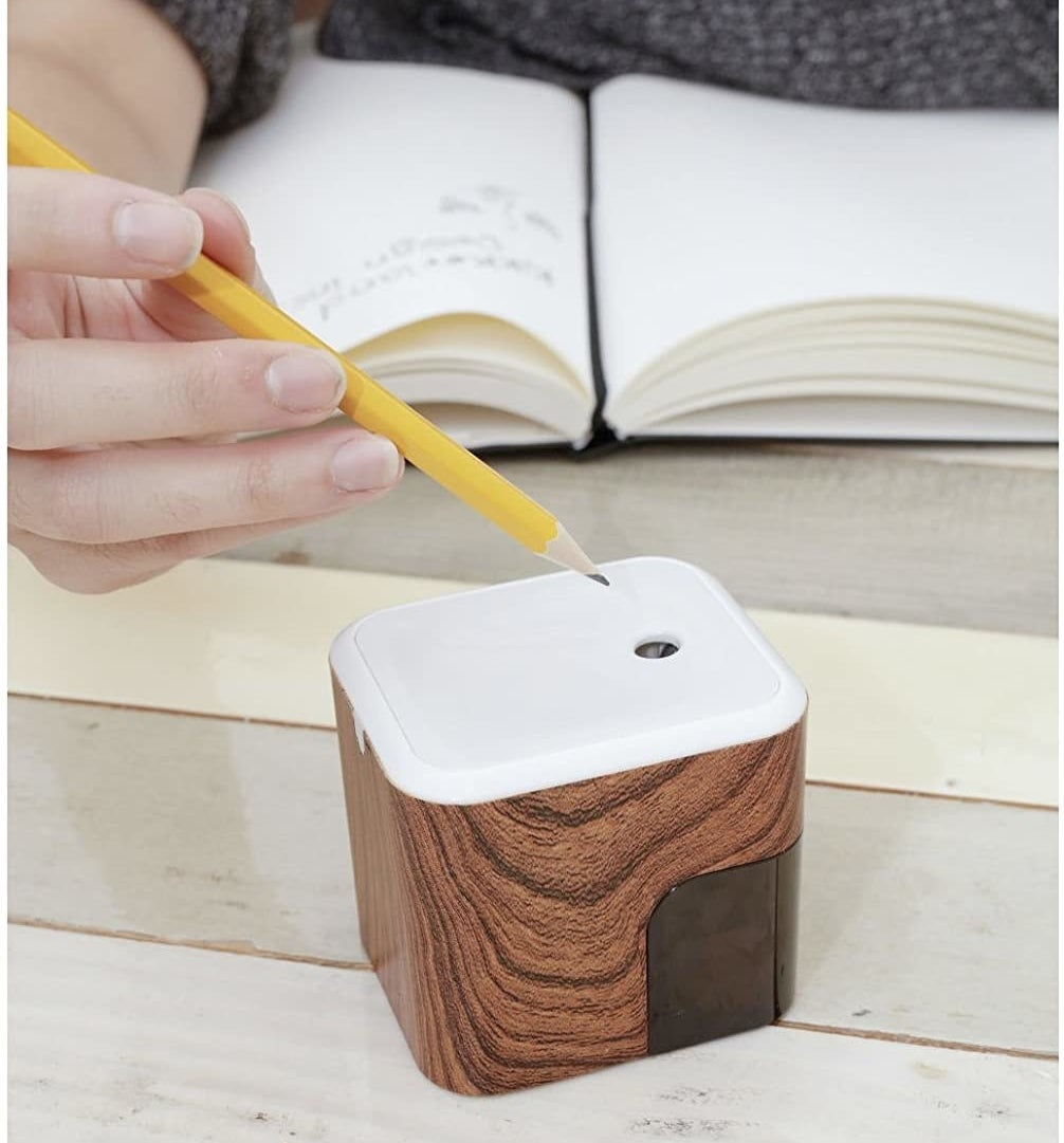 A person putting a pencil into the sharpener