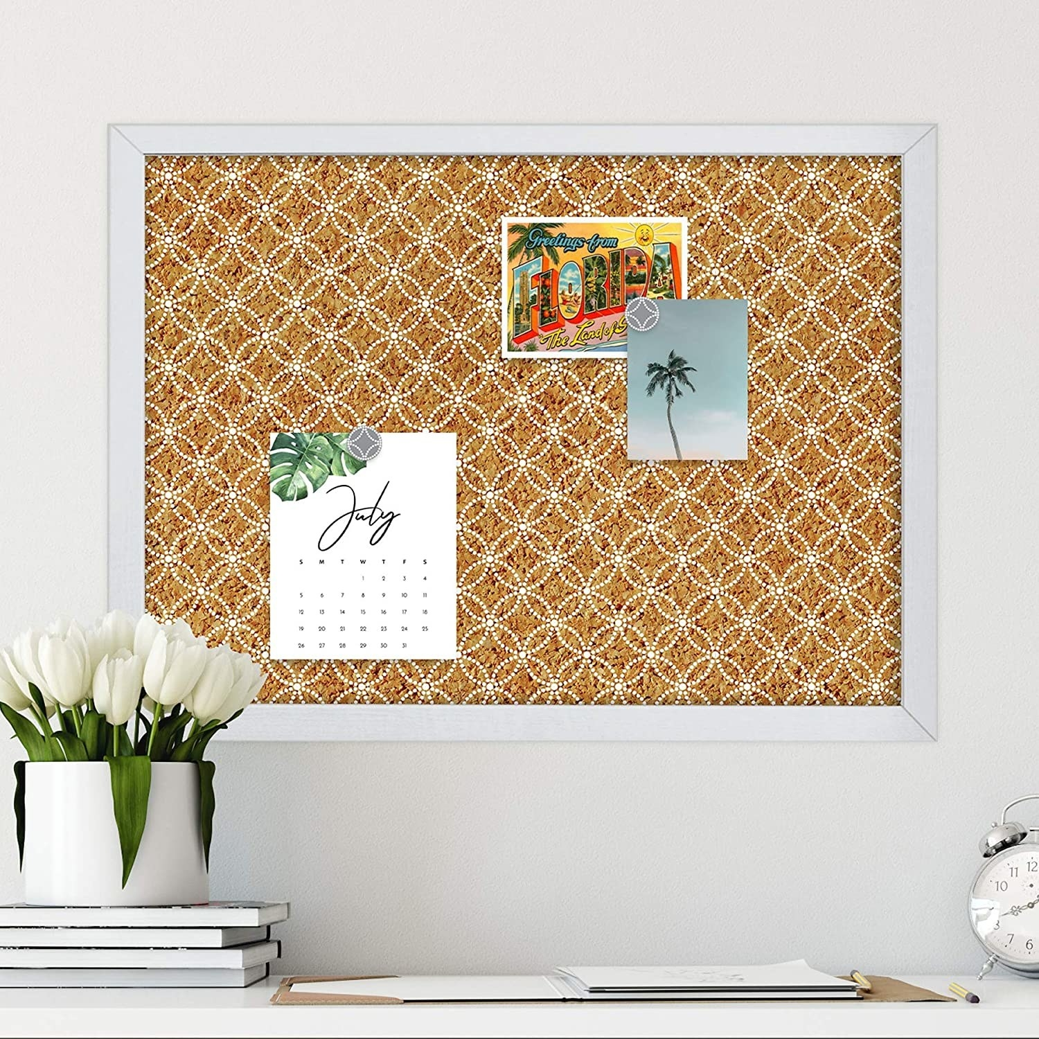 A patterned cork board with postcards and a calendar on it
