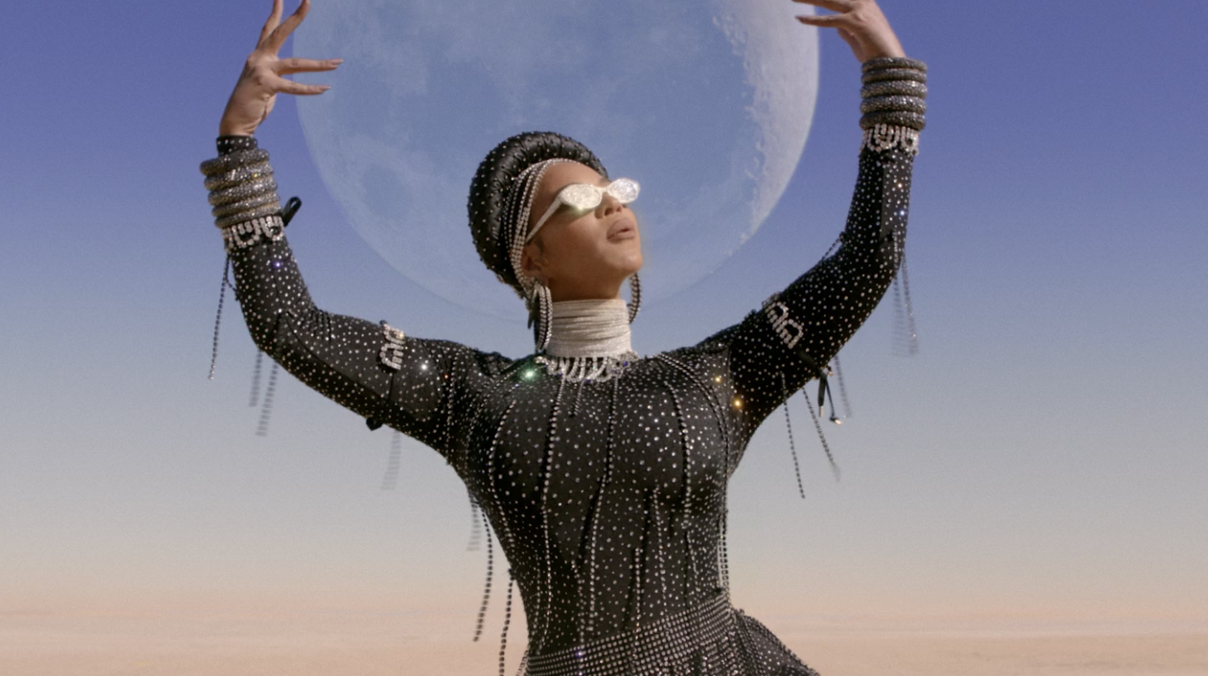 Beyoncé holding up her arms with the moon behind her