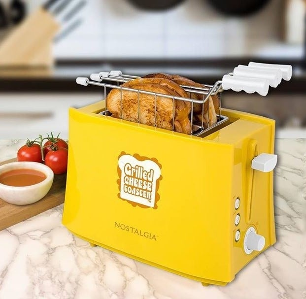 The toaster with two grilled cheese sandwiches inside