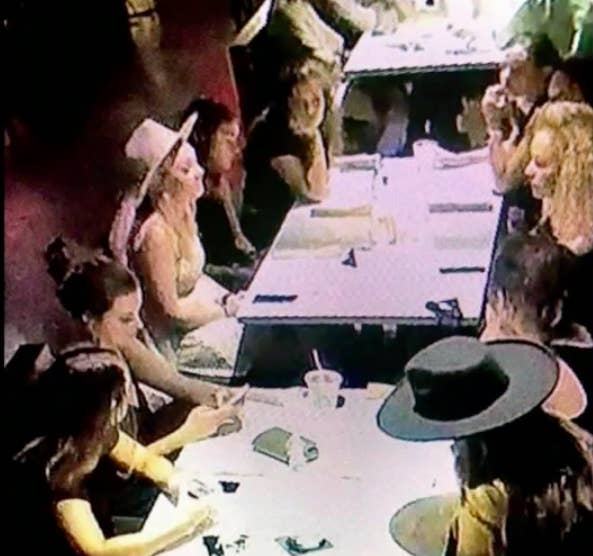 A security camera screenshot of nine women sitting at two tables at the Mockingbird restaurant.
