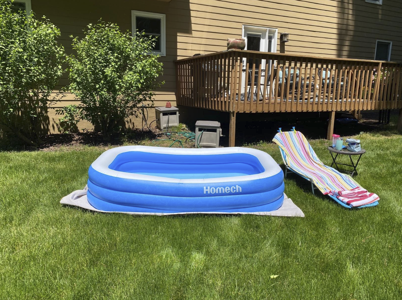 the blow-up pool has a rectangle shape and is sitting in a grassy yard beside a lounging chair and small table with drinks on it