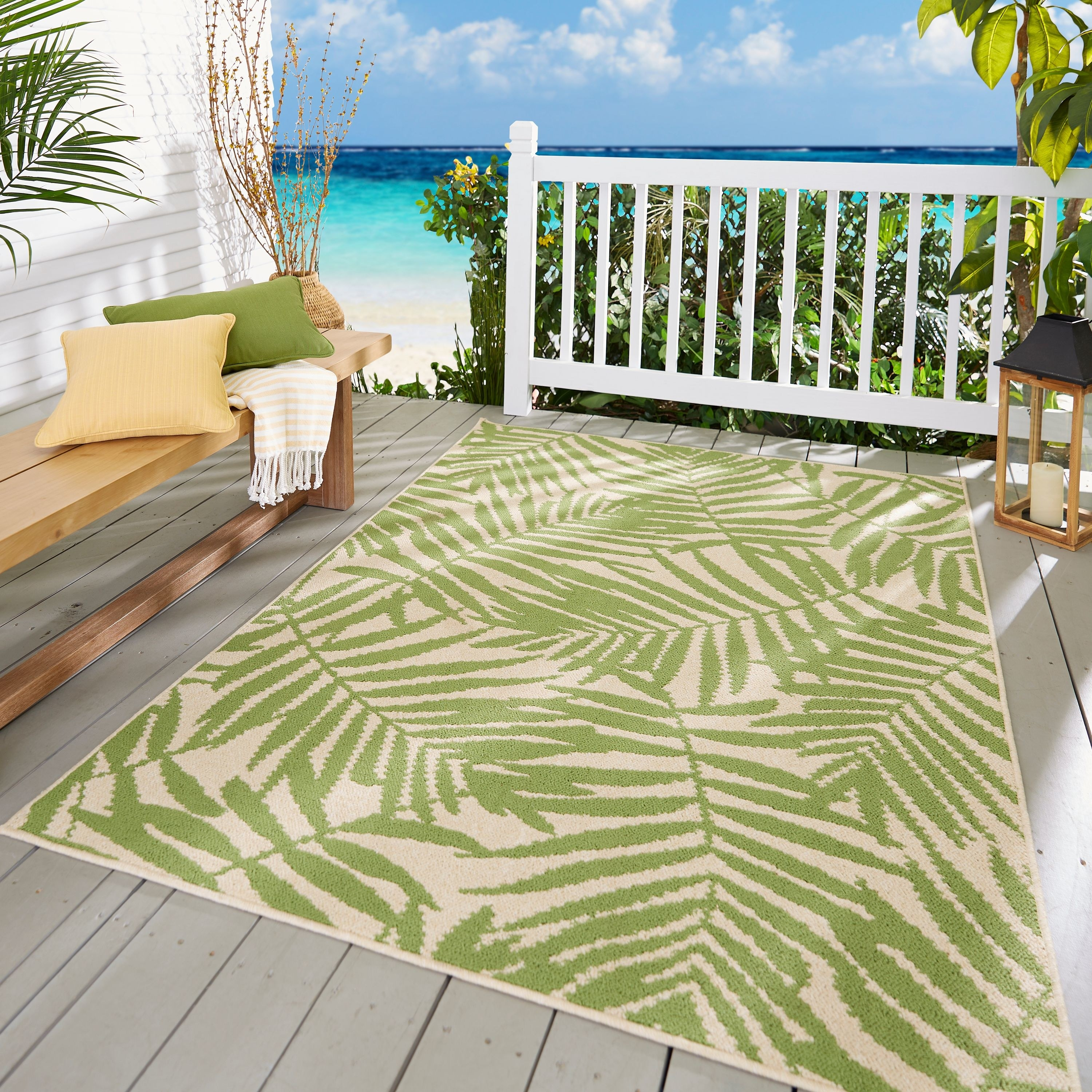 a off white rug with green oversized leaf patterns on it