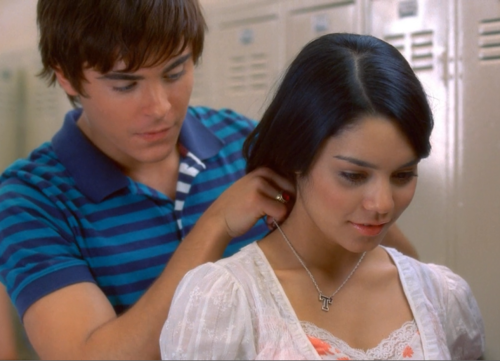 """Troy putting the """"T"""" chain necklace on Gabriella in the hallway at school"""