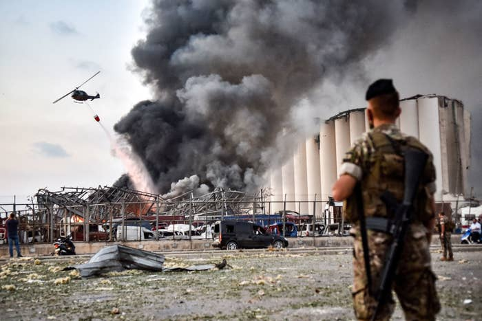 A helicopter douses flames and smoke next to a grain silo