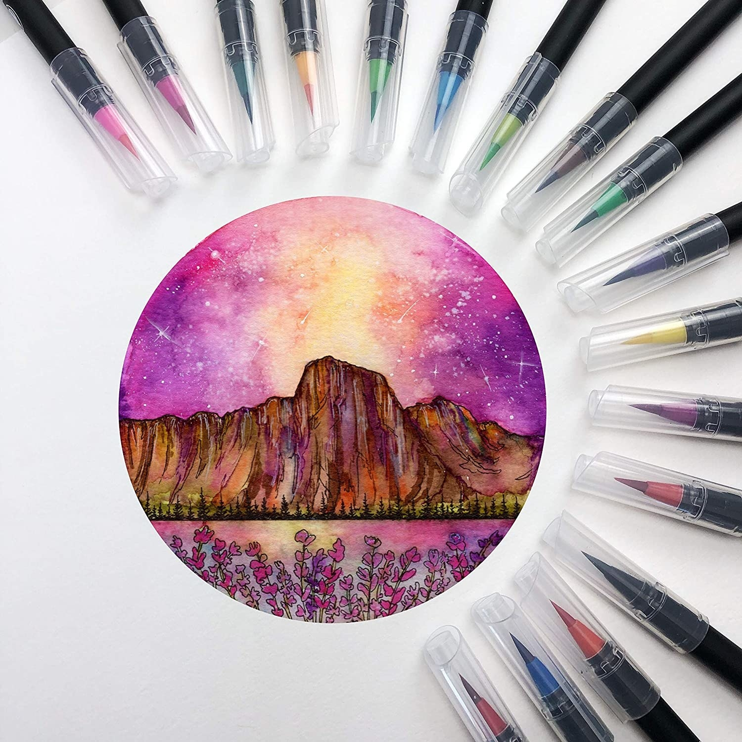 Twenty watercolour brush pens placed around a small drawing of a sun setting behind a mountain