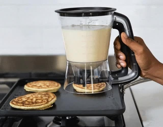 A person dispenses batter onto a hot griddle to make pancakes
