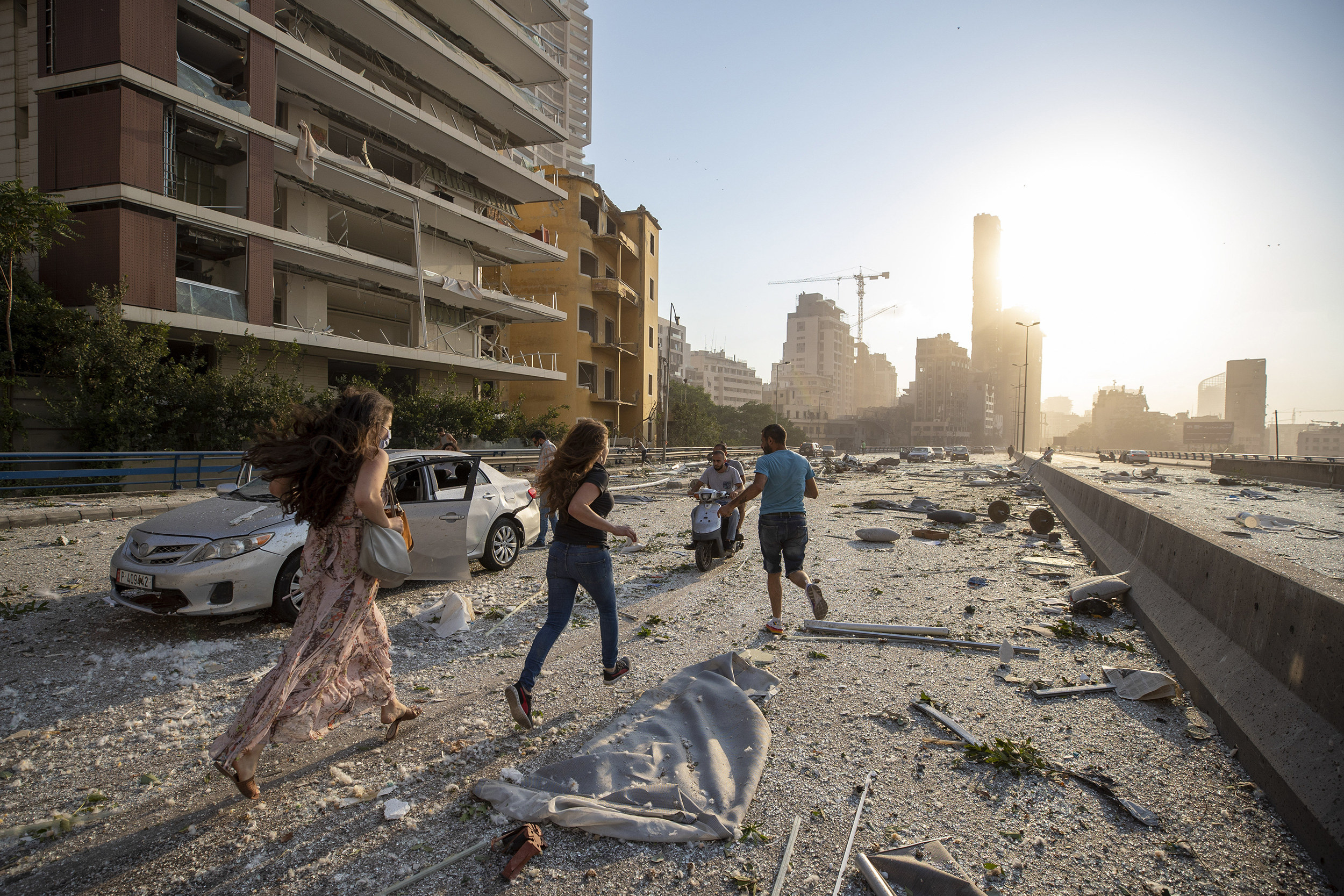 Two women and a man run down a street covered with debris.