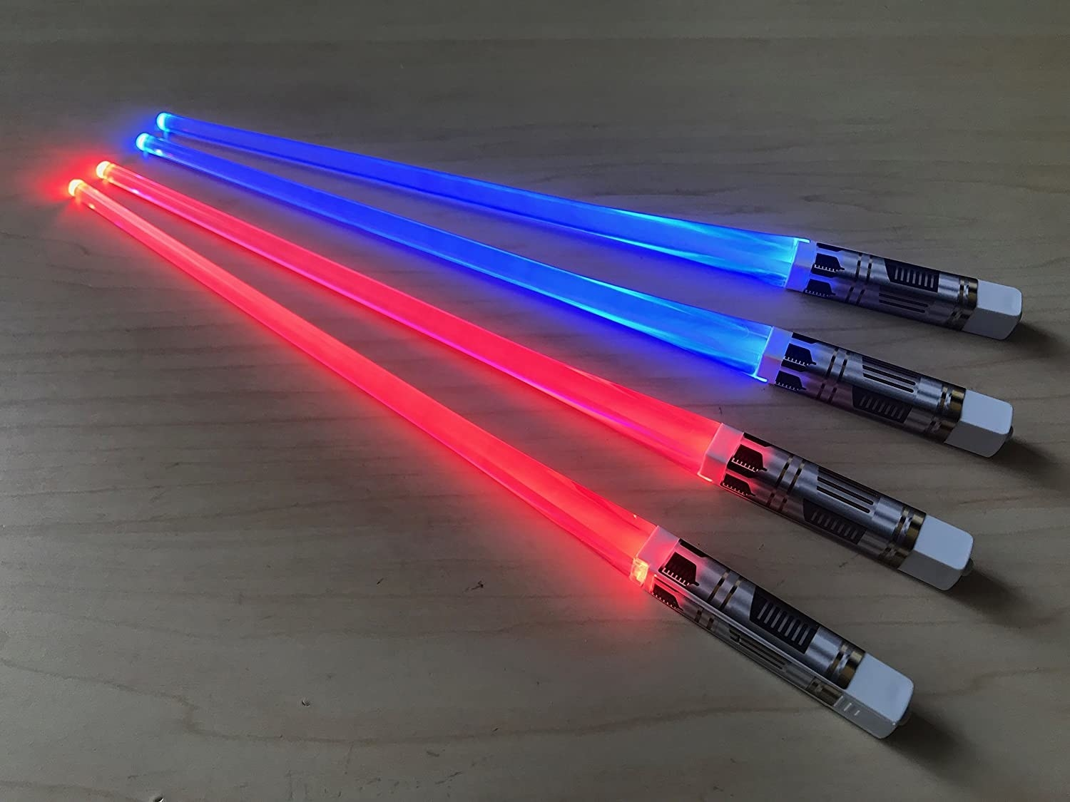 Two pairs of lightsaber chopsticks on a wooden table