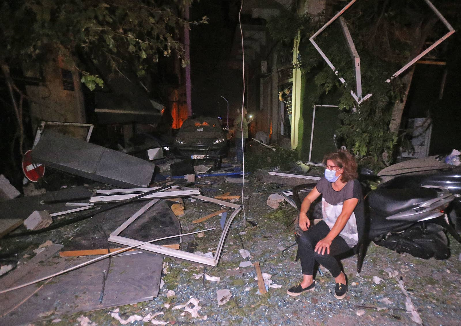 A woman sits on a chair at night on a street covered in glass and debris