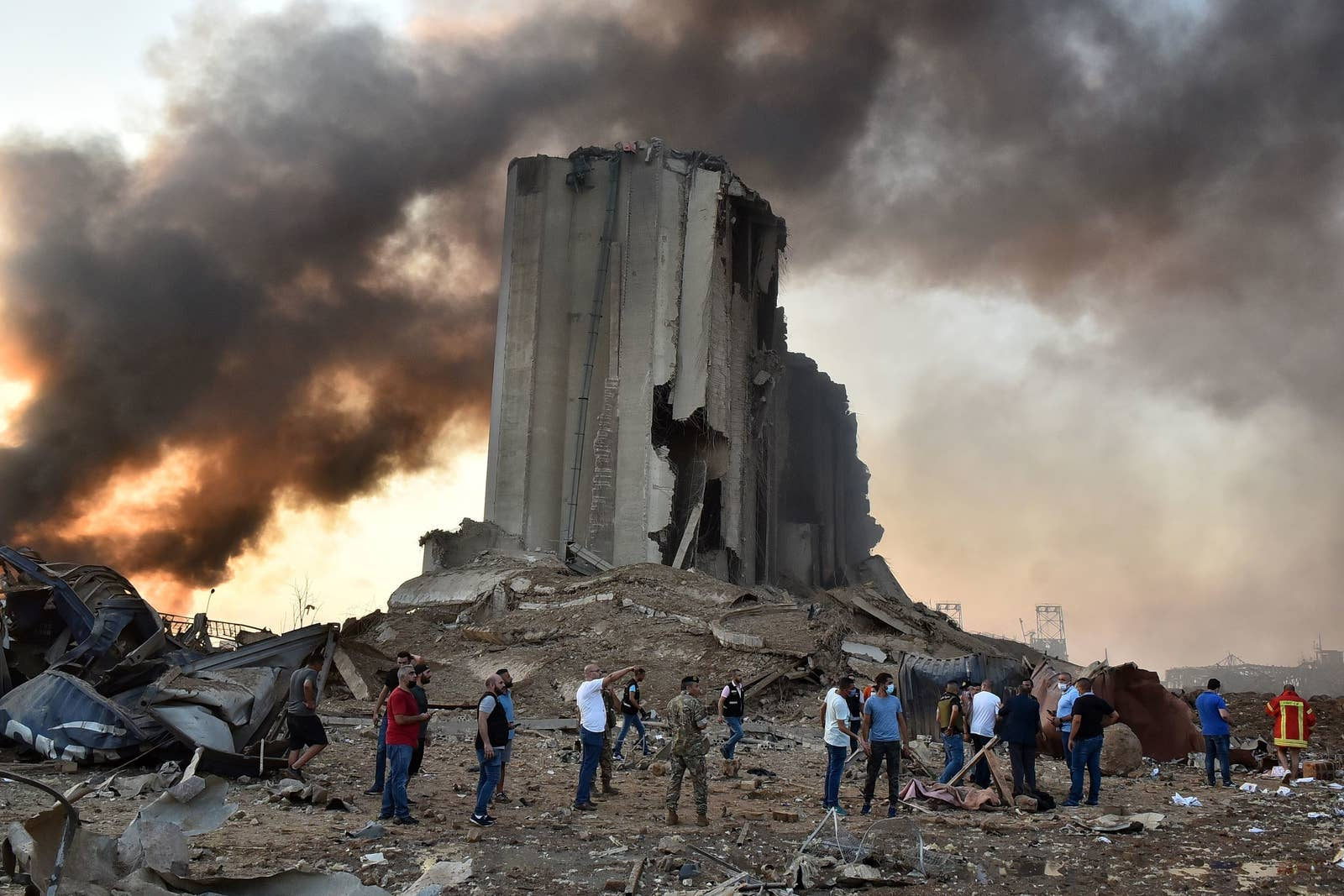Black smoke rises into the air behind a destroyed grain silo, where a crowd of men in masks stand in shock following an explosion