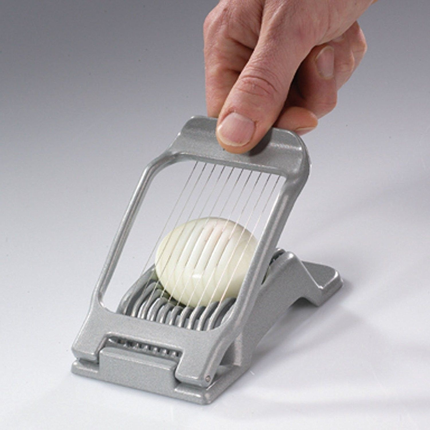 A person presses the egg slicer into a hard boiled egg