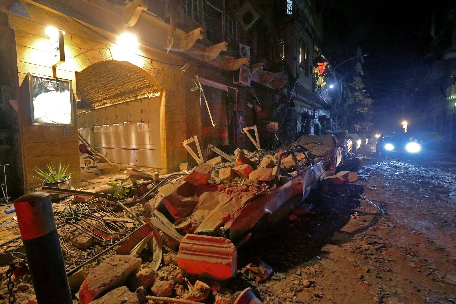 Cars are buried in rubble and buildings destroyed on a street at night