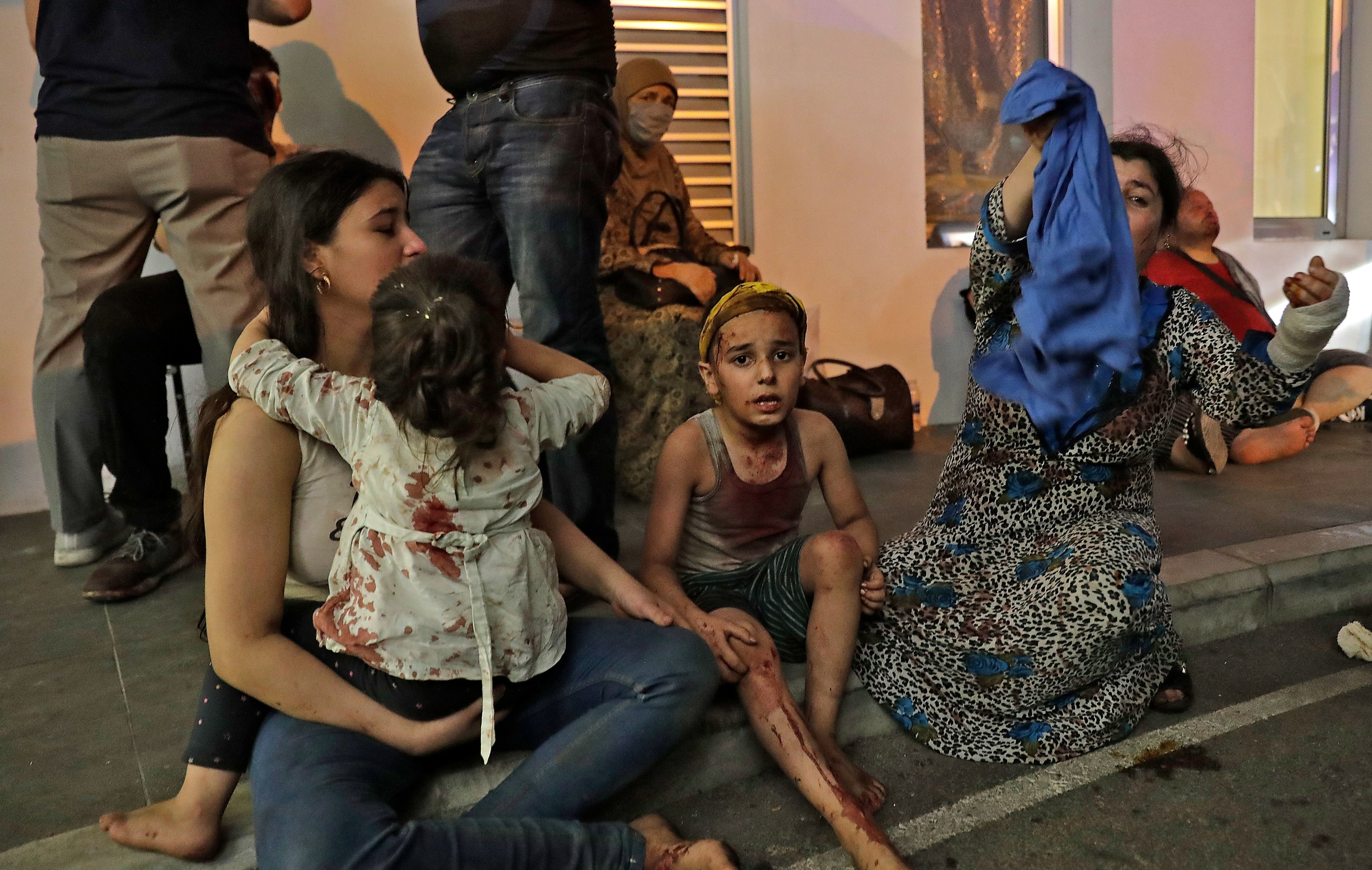 A woman holds her children, who have blood on them, while waiting outside the hospital