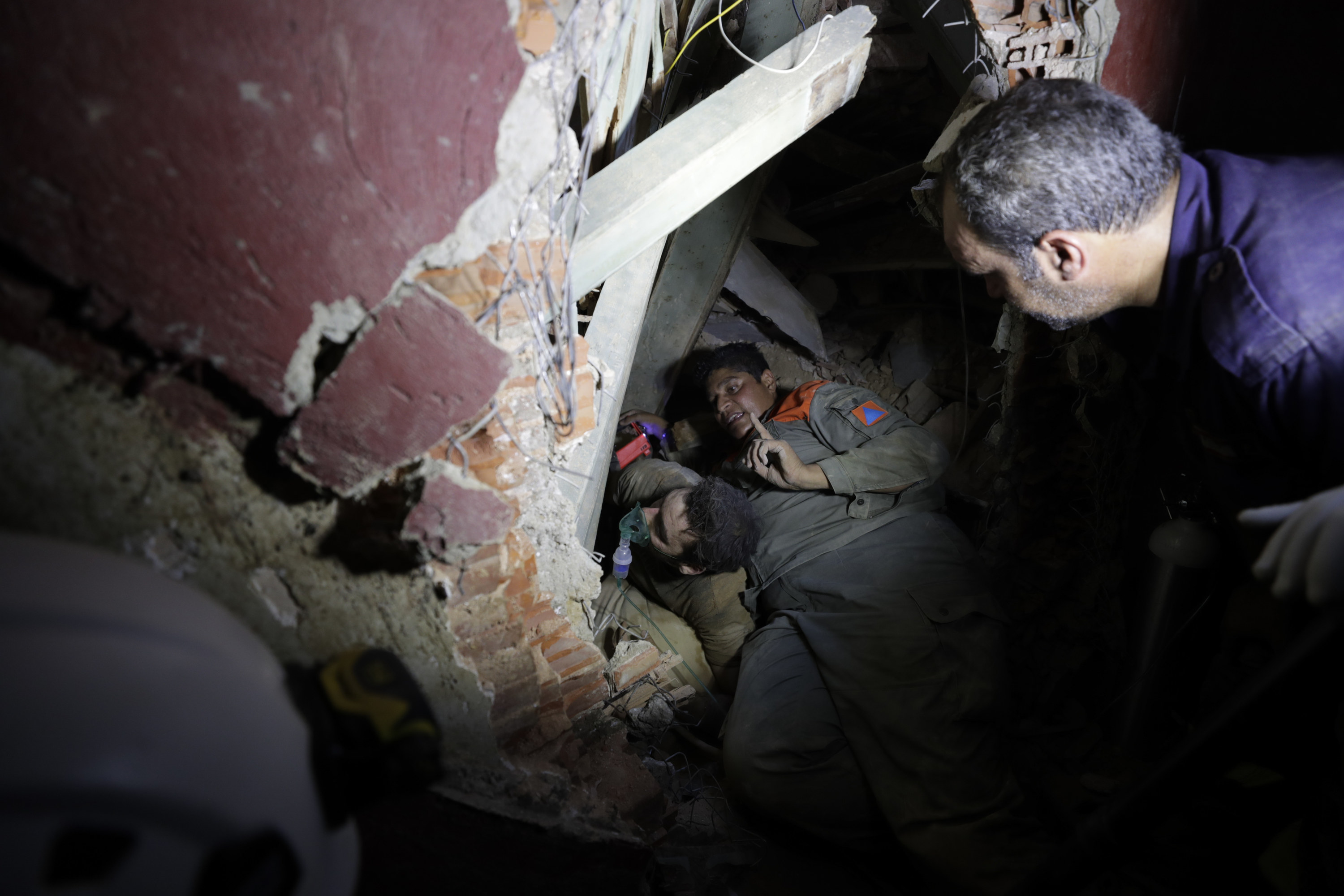 Two soldiers search in a destroyed house for survivors with a flashlight at night