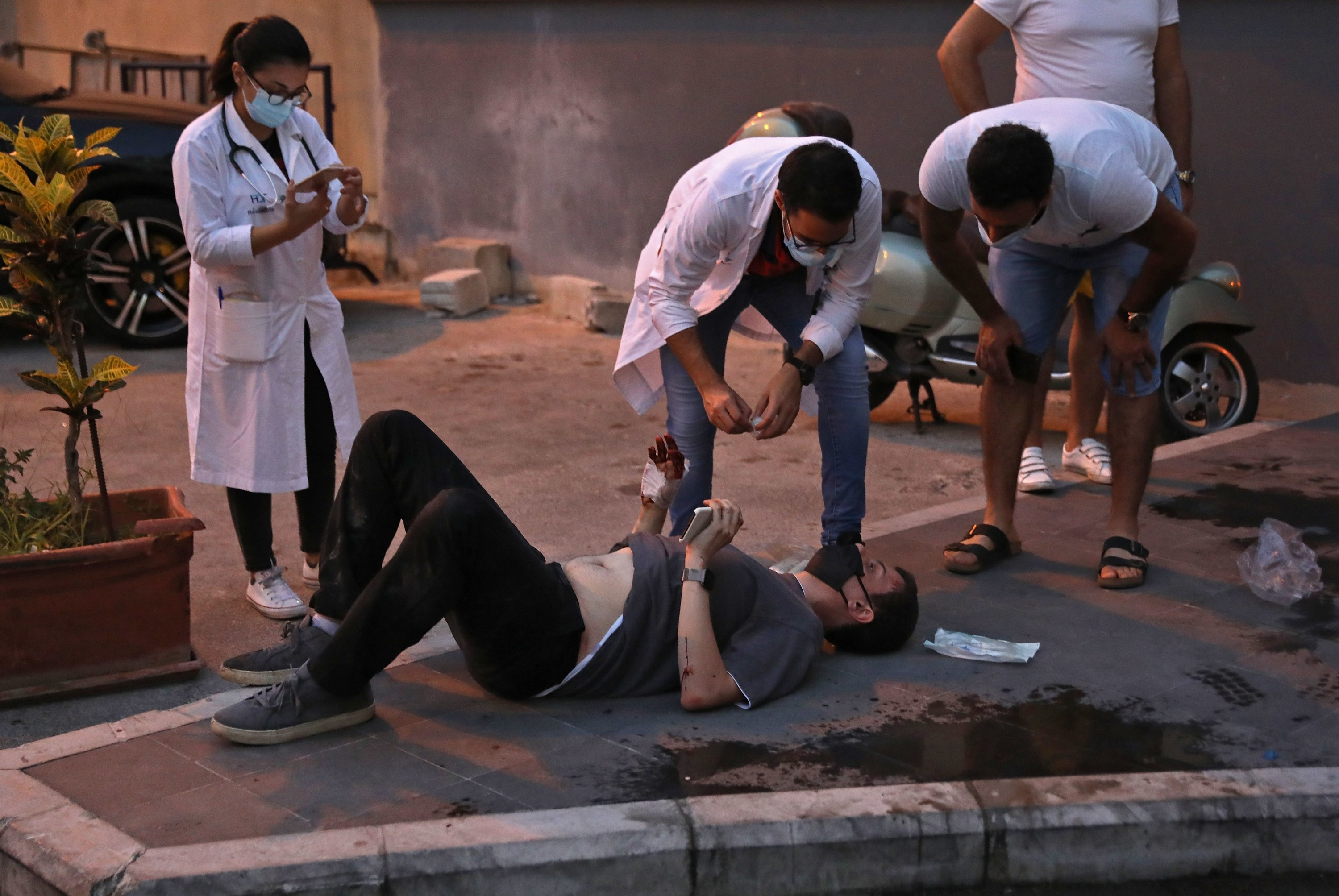 Three doctors in white coats stand over an injured man lying on the ground