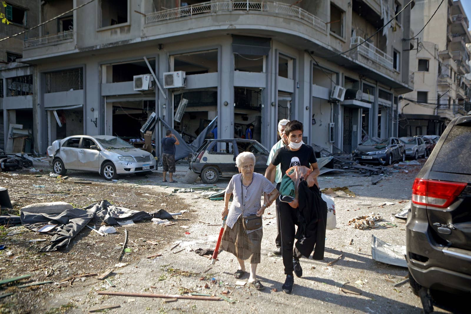 A young man walks an old woman down a destroyed street