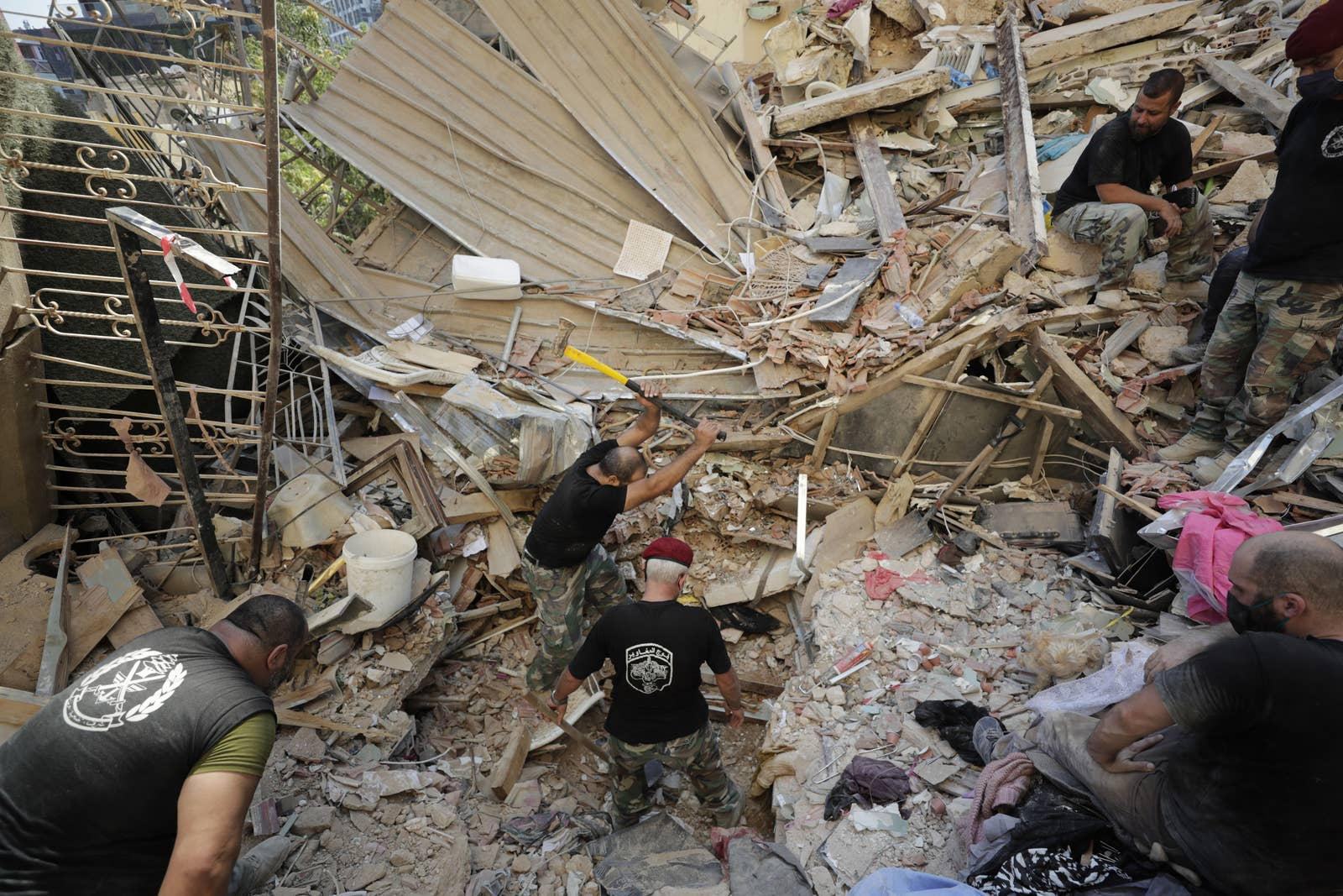Three men in fatigues and T-shirts dig through a massive pile of rubble