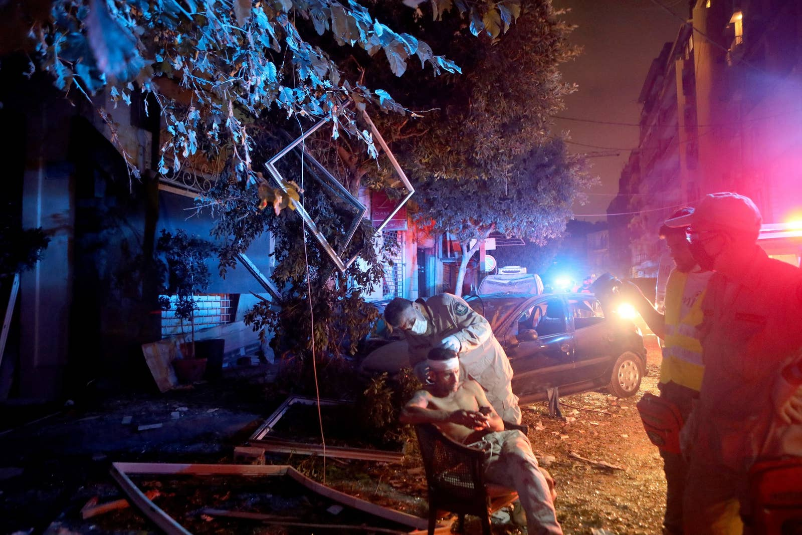 An injured man sits outside under red and white lights at night while a rescue worker examines his bandaged head