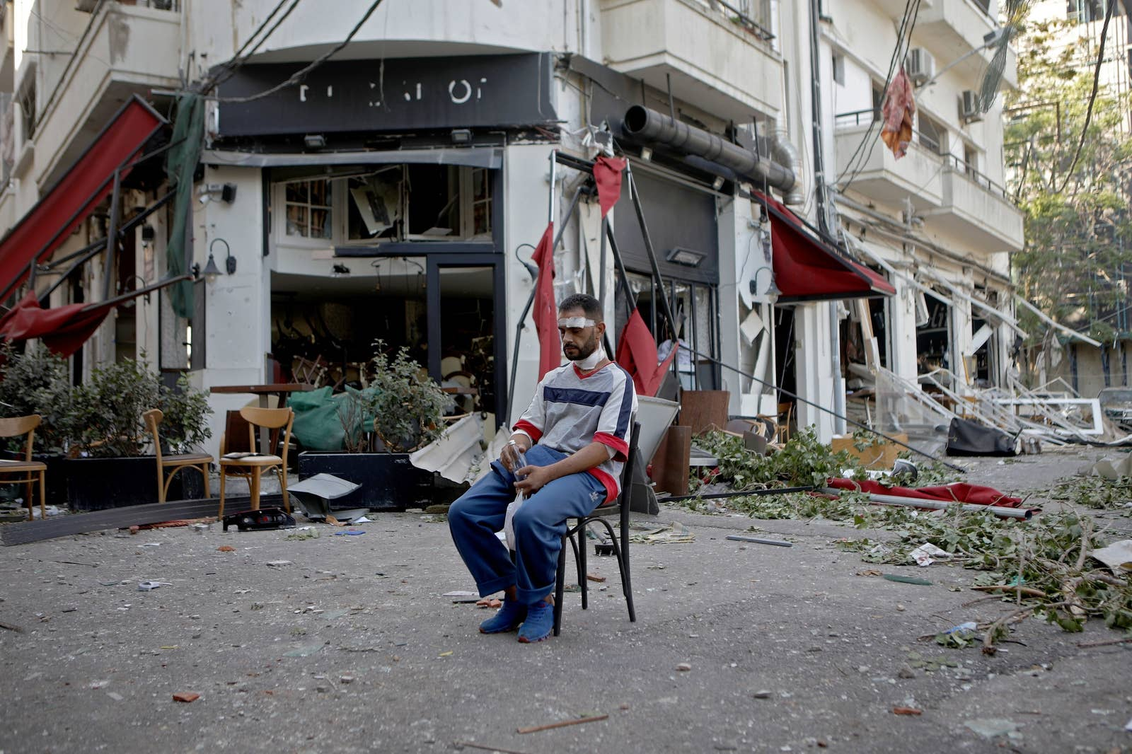 A man with a bandaged head sits in the middle of a destroyed street