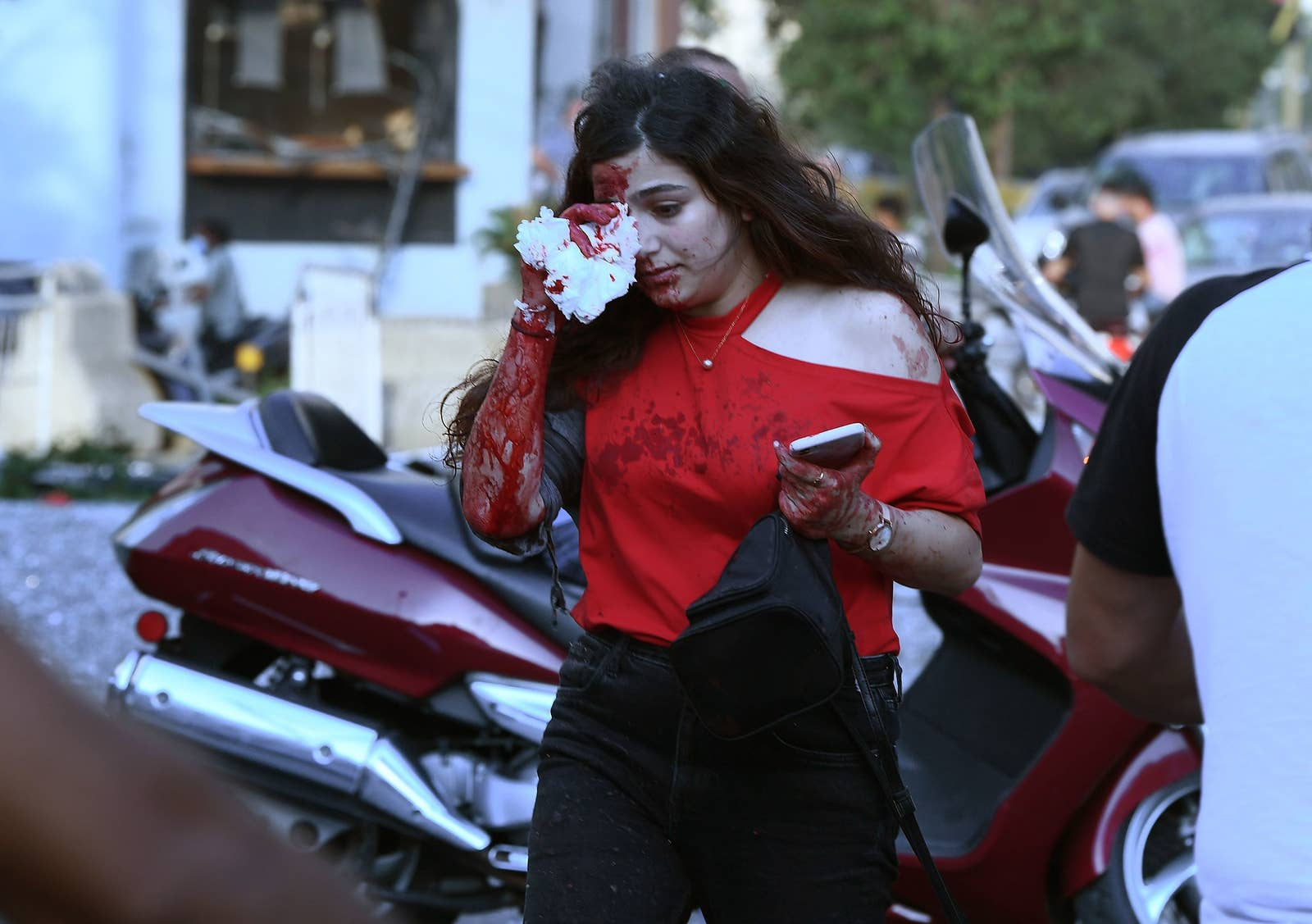 A woman in a red shirt covers her eye, her face, shirt, and arm covered in blood as she walks down the street