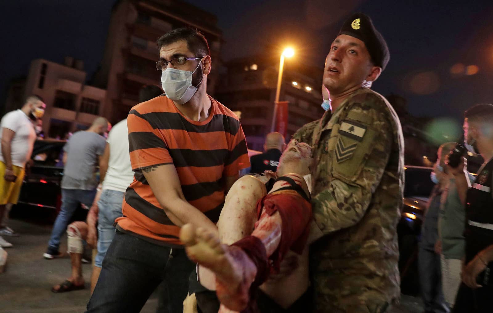 A man in a striped shirt and a mask carries a person with a leg injury down a crowded street with the help of a Lebanese soldier in uniform