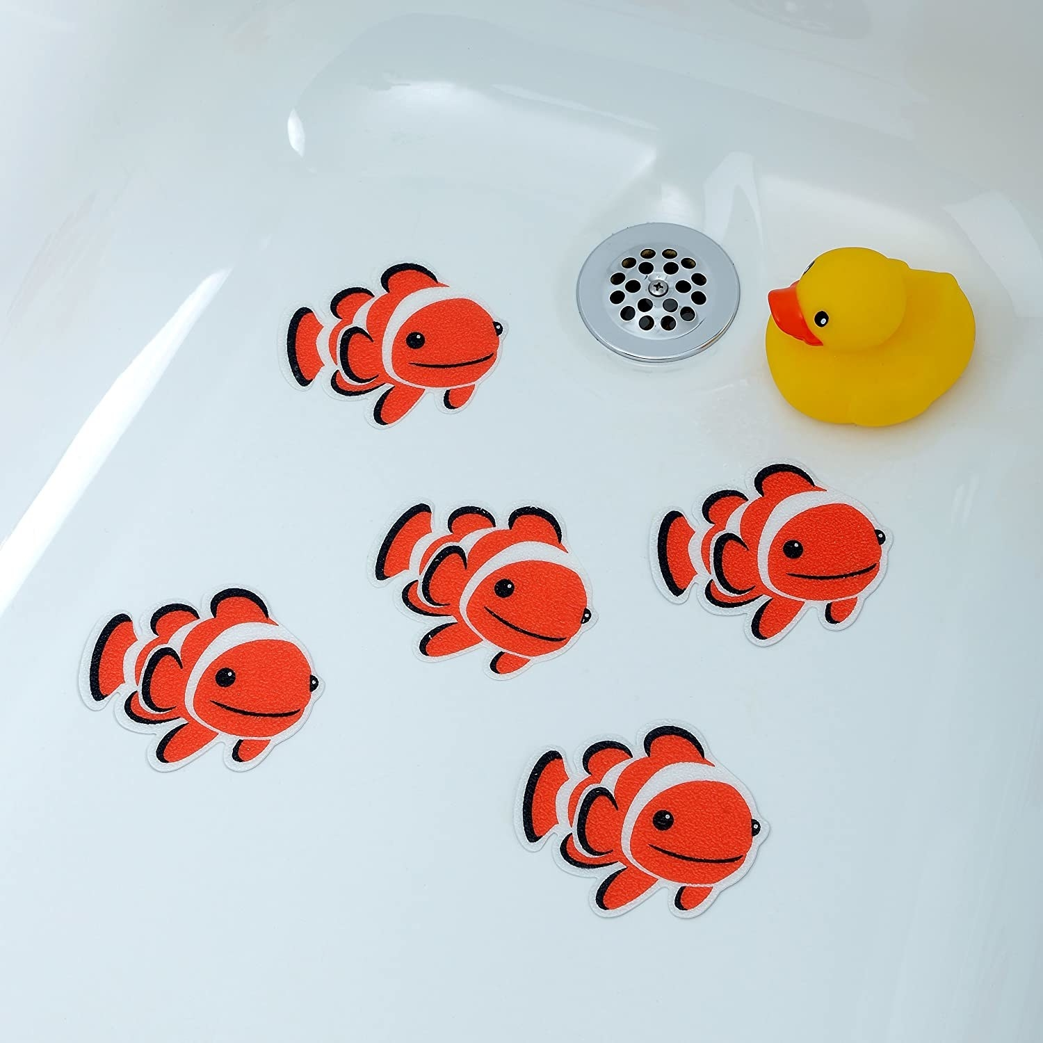 Five clownfish tub stickers on the bottom of a bathtub with a rubber ducky