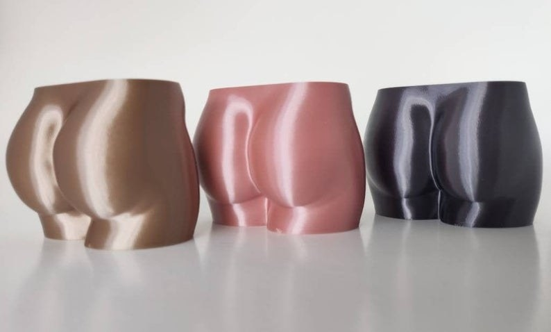 three butt-shaped planters in gold, pink, and black
