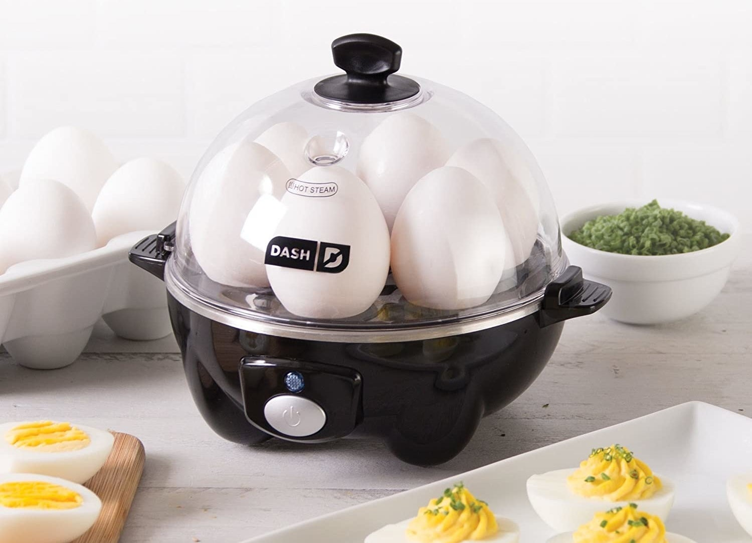 The egg cooker in black filled with six eggs