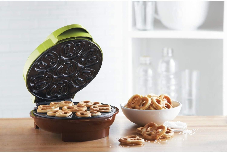 The open pretzel maker with fresh pretzels inside and a bowl of salty mini pretzels next to it