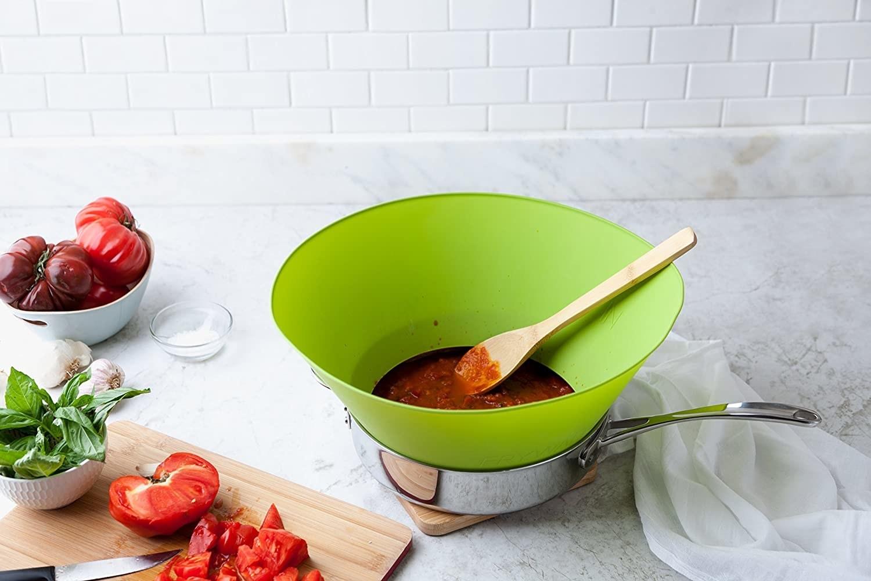 green cone-like Frywall on pot of marinara sauce on tidy countertop