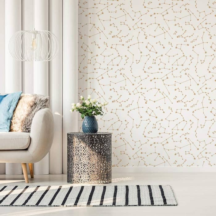 A living room with one wall covered in the Novogratz Constellations Removable Peel and Stick Wallpaper in Frost.