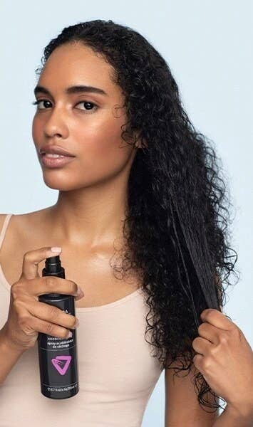 A model applying the spray to their damp, curly hair