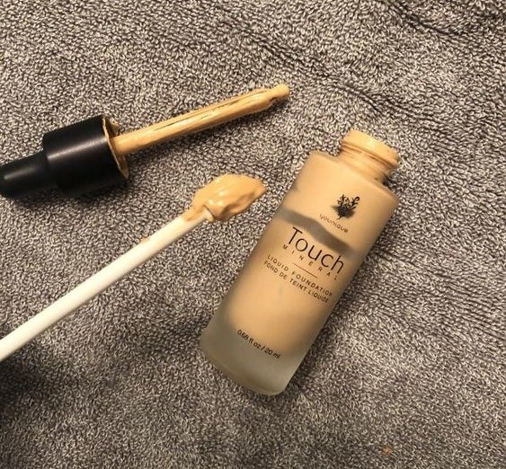 Reviewer's picture of the scraper helping them empty their foundation bottle