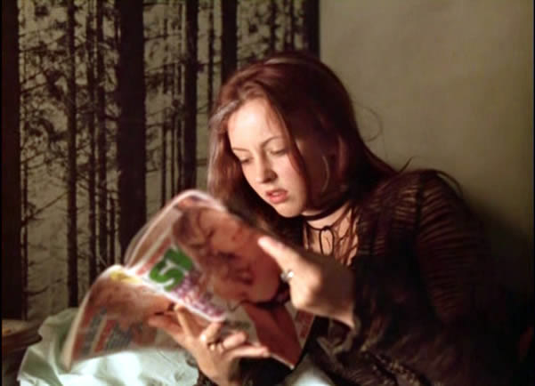 Ginger reads a magazine with a woman on the cover