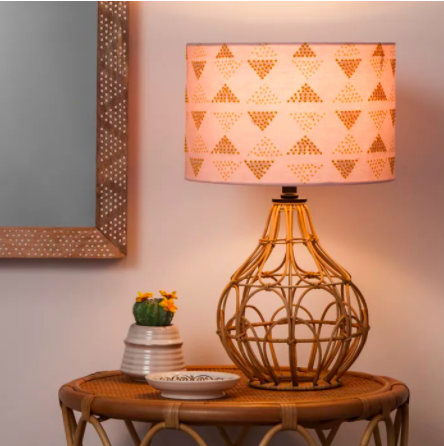 rattan base lamp with light pink and geometric shape lamp shade on a side table