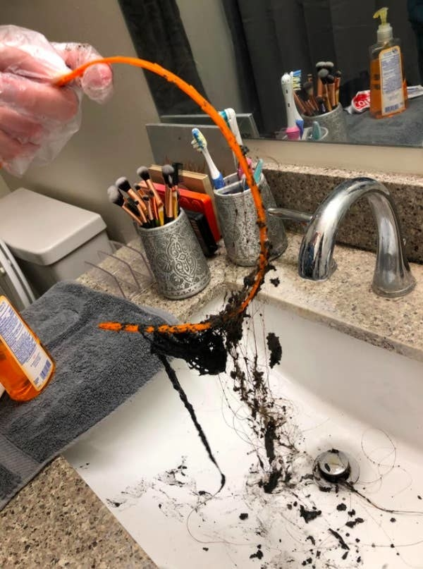 A reviewer using the drain snake to remove hair from their drain