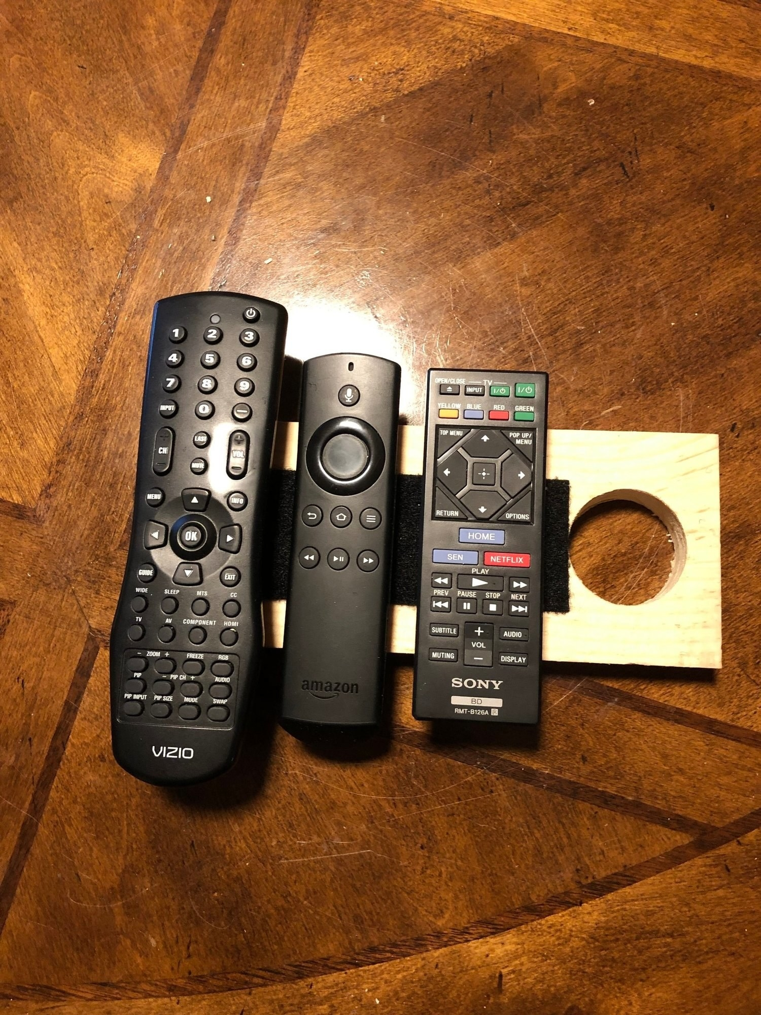 Velcro holding remote controls on a piece of wood that can hang off a doorknob