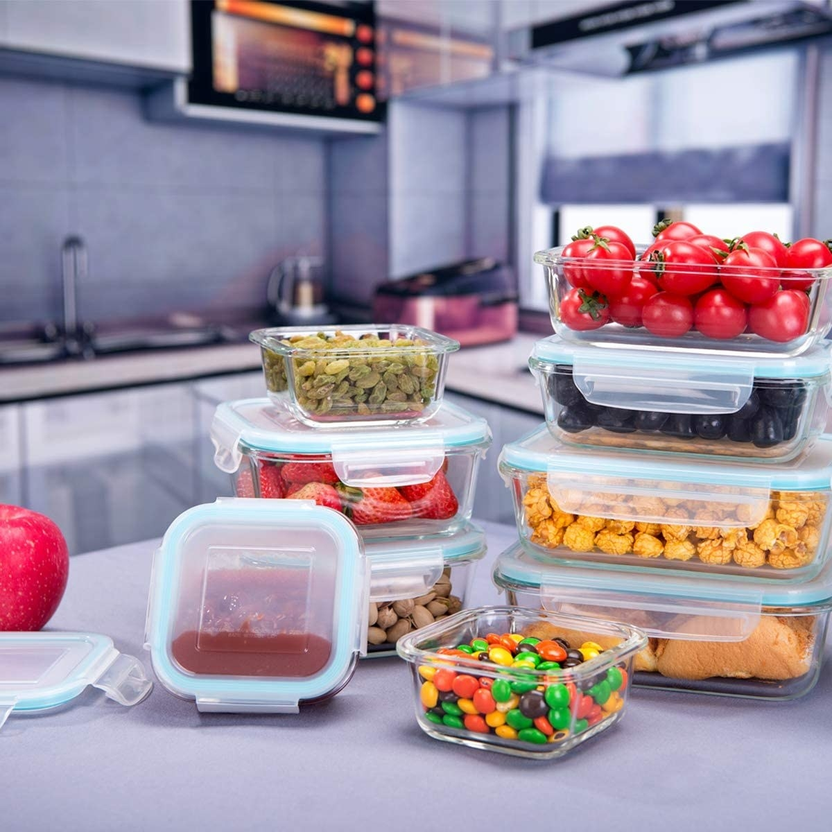 The glasses food storage containers in assorted sizes filled with different kinds of food on a counter