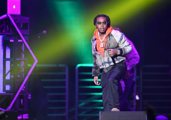 Takeoff stands onstage, wearing a hoodie, chain necklace, and jacket and holding a microphone