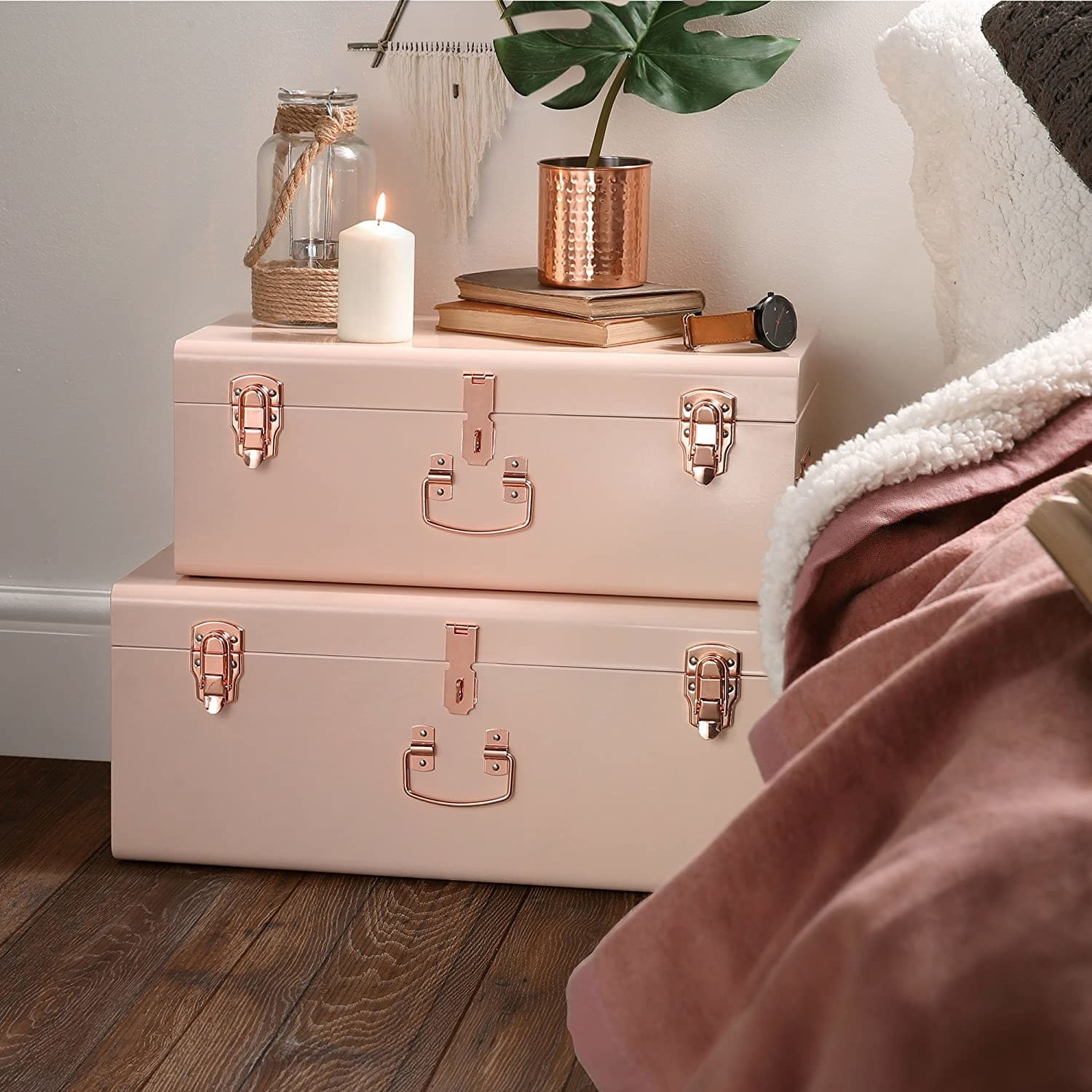stack of three blush storage trunks with gold tone hardware used as a night stand