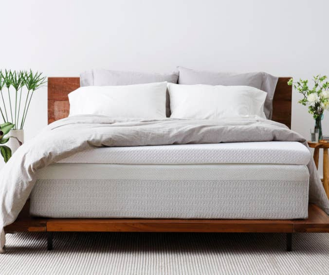 White mattress topper on top of a wooden bed with a white duvet cover