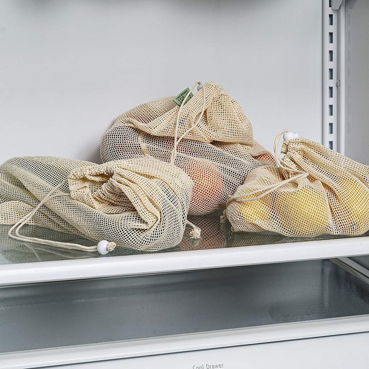 Several bags of produce organized inside the mesh bags inside a refrigerator