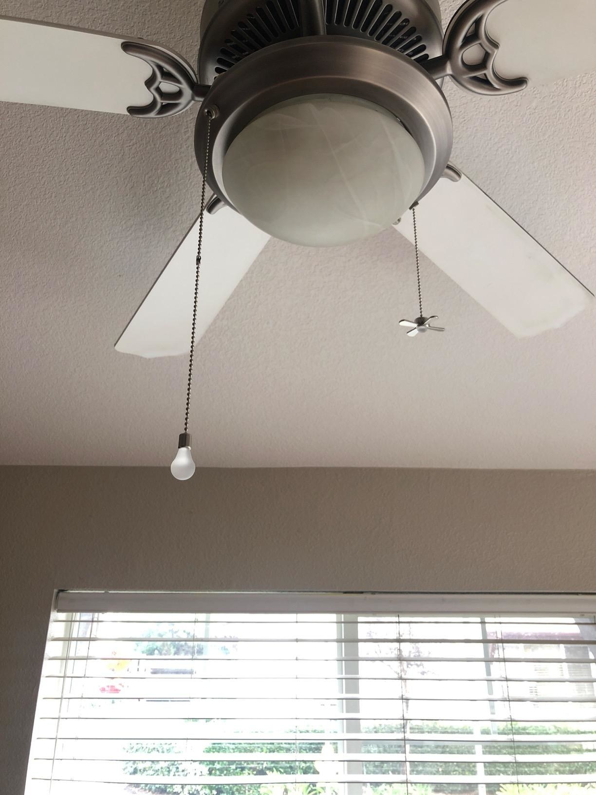 ceiling fan with two charms shaped like fan and lightbulb